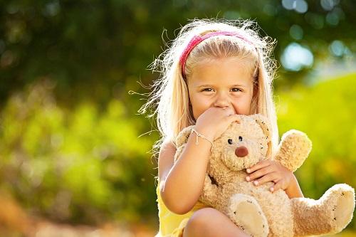 Beautiful little girl sitting outdoors holding a teddy bear.